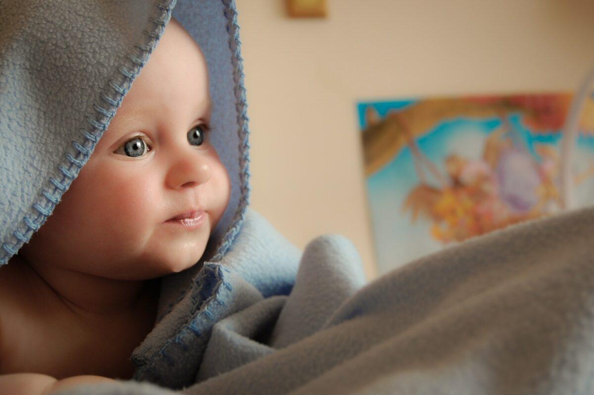 widoczna buzia małego dziecka, głowa pod niebieskim kocem