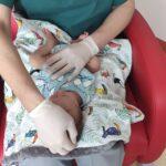 badanie noworodka - dłonie na głowie
